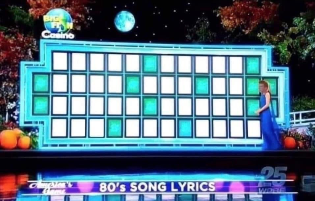 """A wheel of fortune board with no letters. the topic for the puzzle is in a banner across the bottom of the screen """"80's SONG LYRICS"""""""